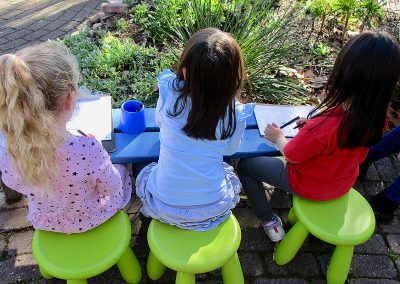Three children sitting and drawing out in the backyard