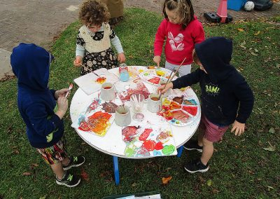 Children painting out on the backyard